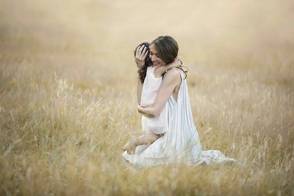 Family Photography London | portrait of mum hugging her 3 years old daughter in the middle of long dry grass field