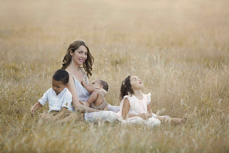 Family Photography London | portrait of a mum and her 3 children taken during breasfeeding time in a long dry grass field
