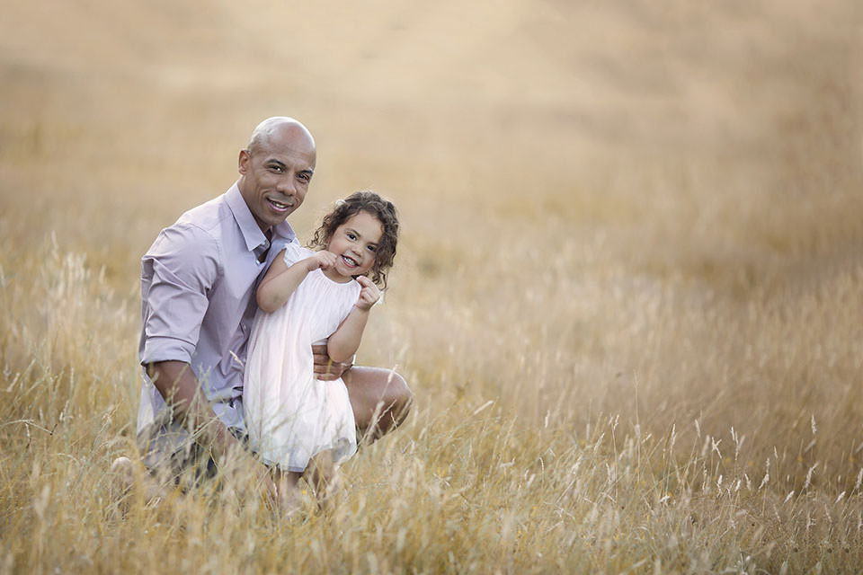 Family Photography London | photo of a father and hid 3 year old daughter taken during the professional photo session in long dry grass field