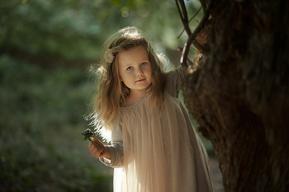 Kids Photography London | stunning backlit outdoor portrait of a girl holding a small bunch of spring flowers