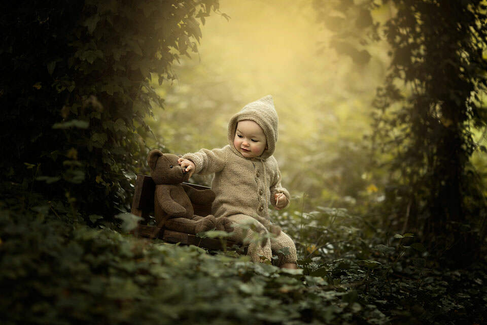 Toddler Photography London | photo of a 1 year old boy playing with a teddy bear in the woodladns taken during professional photo session