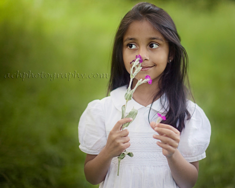 London kids portraits | 5 years old girl smelling pink flower and wearing timeless white dress