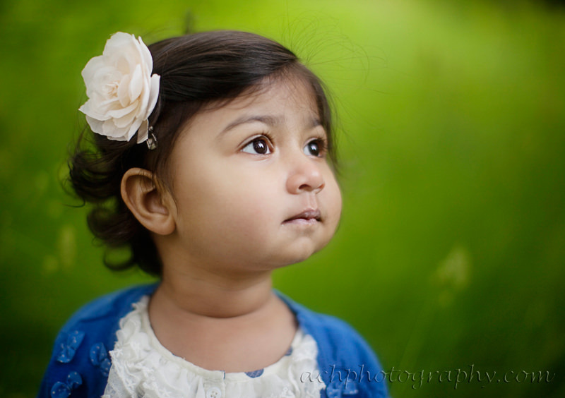 London toddler photo session | toddler girl wearing a flower in her hair and looking away