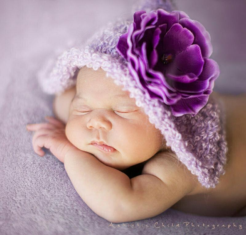 London Newborn Photo Session  | newborn baby girl wearing purple hat with hugle purple flower