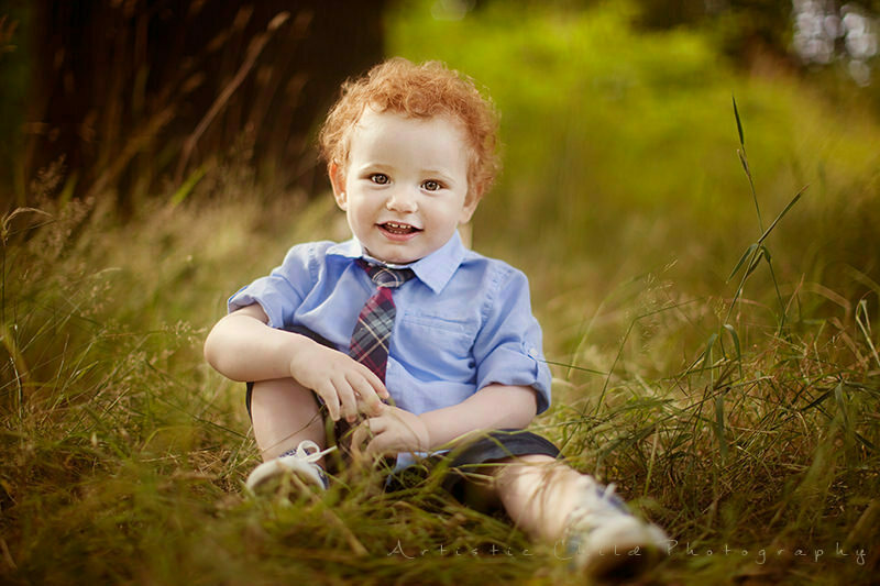 Outdoor London Child Photo Session | 1.5 year old boy sitting in the grass and smiling