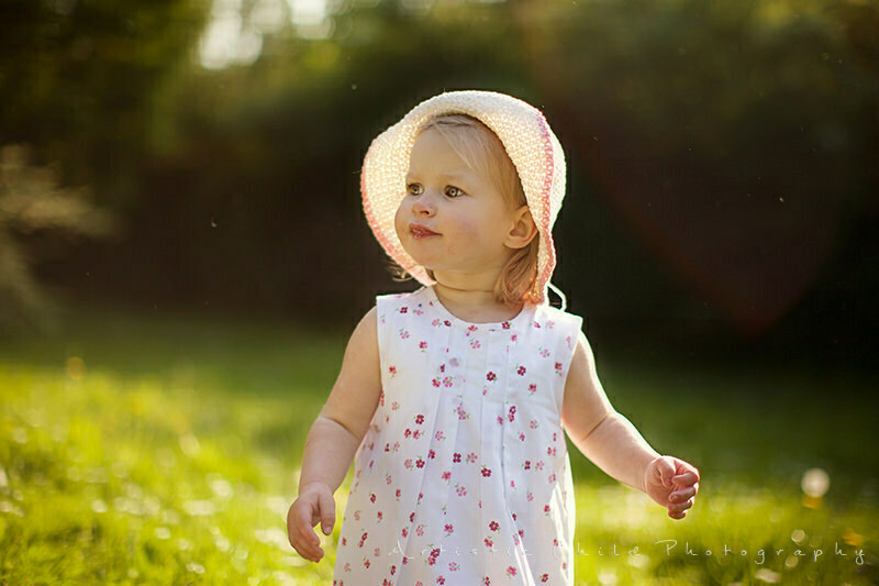 portrait of a toddler girl wearing a straw hat in the park | South East London
