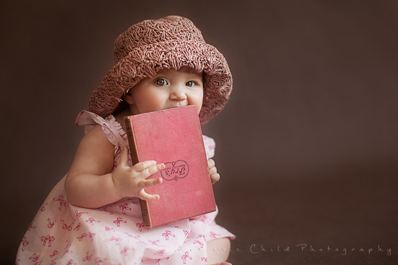 London | portrait of a baby girl biting on a book
