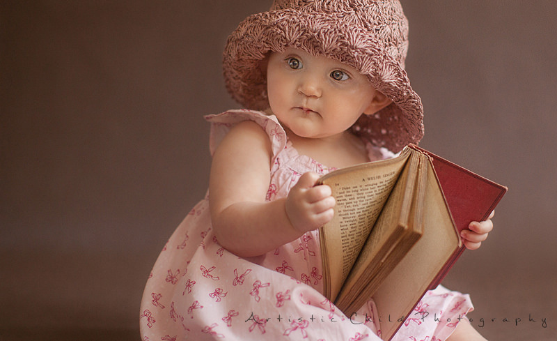 London | a photo of a baby gril playing with the book
