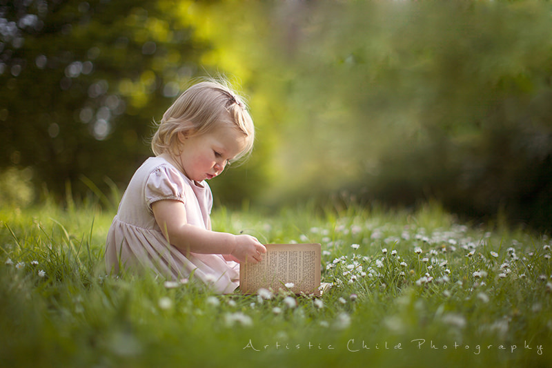 London Toddler Pictures | 17 month old girl sitiing on the grass and reading a book in Crystal Palace Park