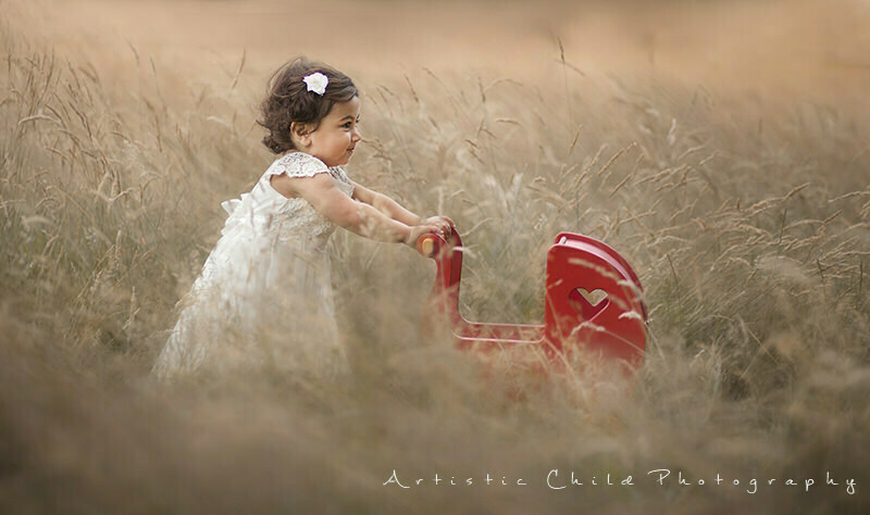 Children Photography in Richmond | London | 15 month old girl walking in the grass with red wooden pram