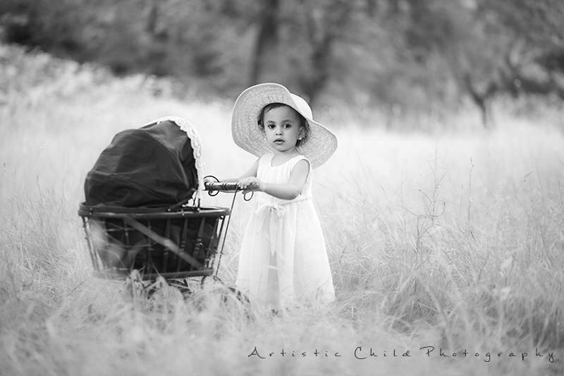 Black and white portrait of 2 years old girl with vintage pram | London
