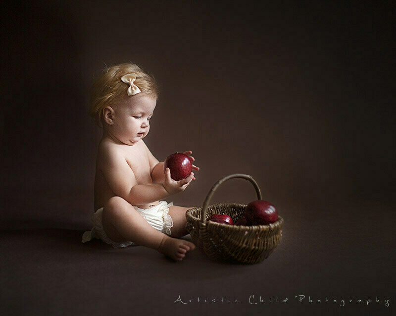 Best London Baby Photography | 9 months old baby girl playing with apple basket during photo session