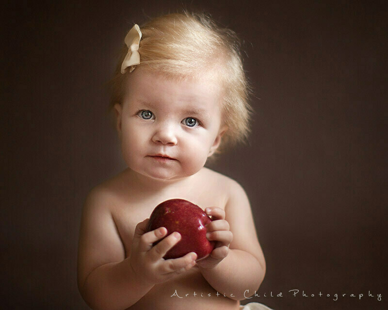 Best London Baby Photography | georgous portrait of 9 months old baby girl with red apple