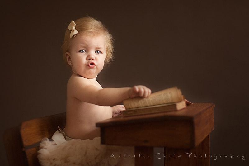baby girl browsing through a book | London