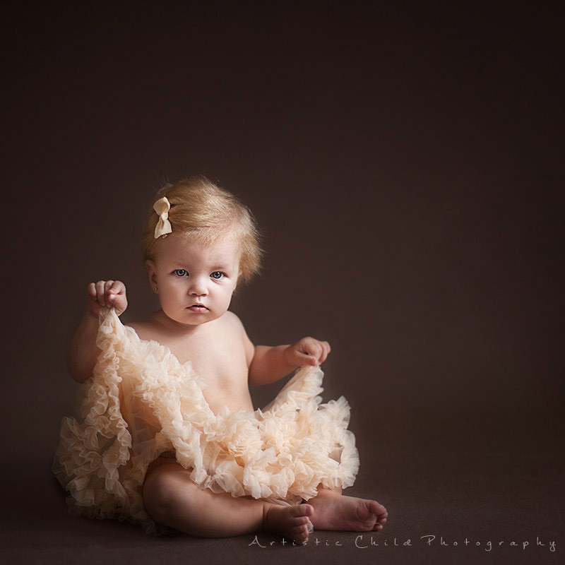 9 month old baby gril playing with her cream tutu | London