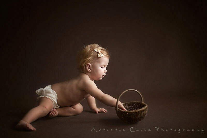 baby girl playing with wicker basket during photo session | London