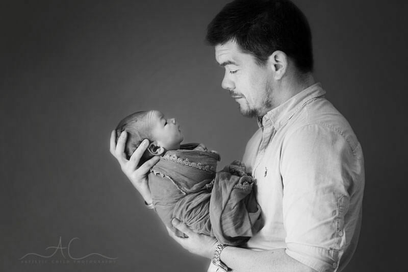 black and white portrait of father looking at his newborn baby boy| London
