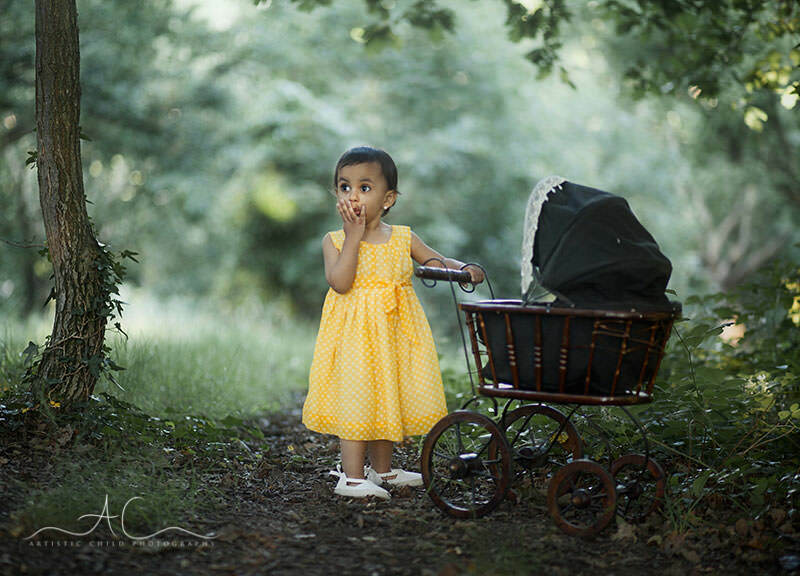 Top London Toddler Pictures | 2 years old toddler girl playing with old pram in the park