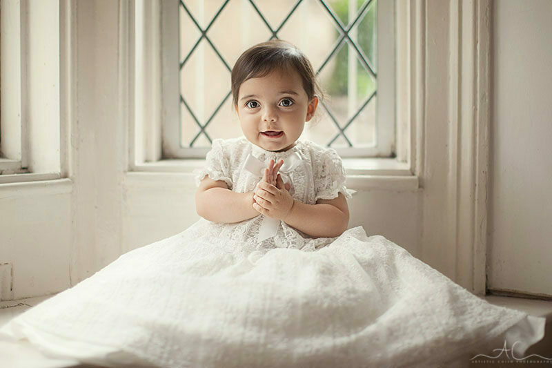baby girl clapping her hands and wearing Christening gown| London