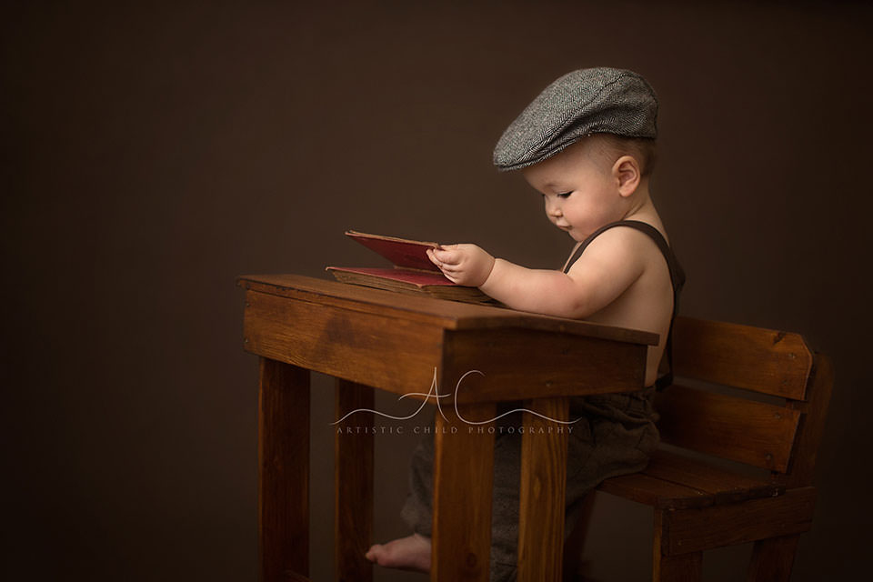 8 months old baby boy in flat cap reading a book | London