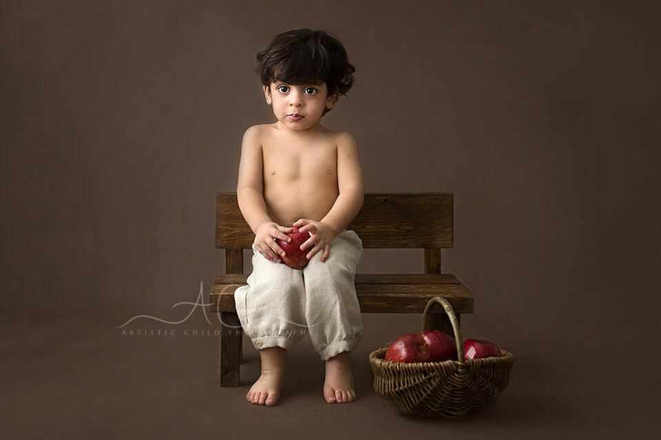 2 year old toddler boy seating on the wooden bench and holding an apple | London