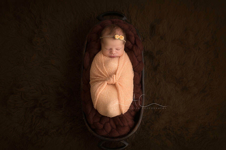 Professional London Newborn Photo Session | newborn baby girl photographed in brown and peach tonality lies down in trench bowl