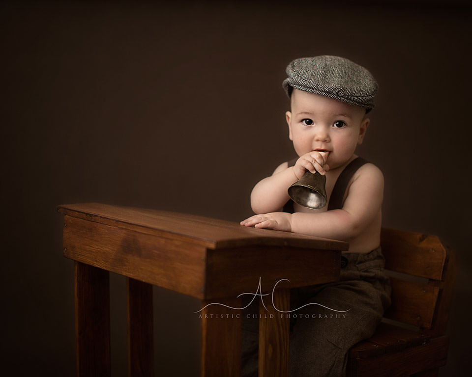 South East London Baby Photographer | baby boy seating at the desk and holding a bell