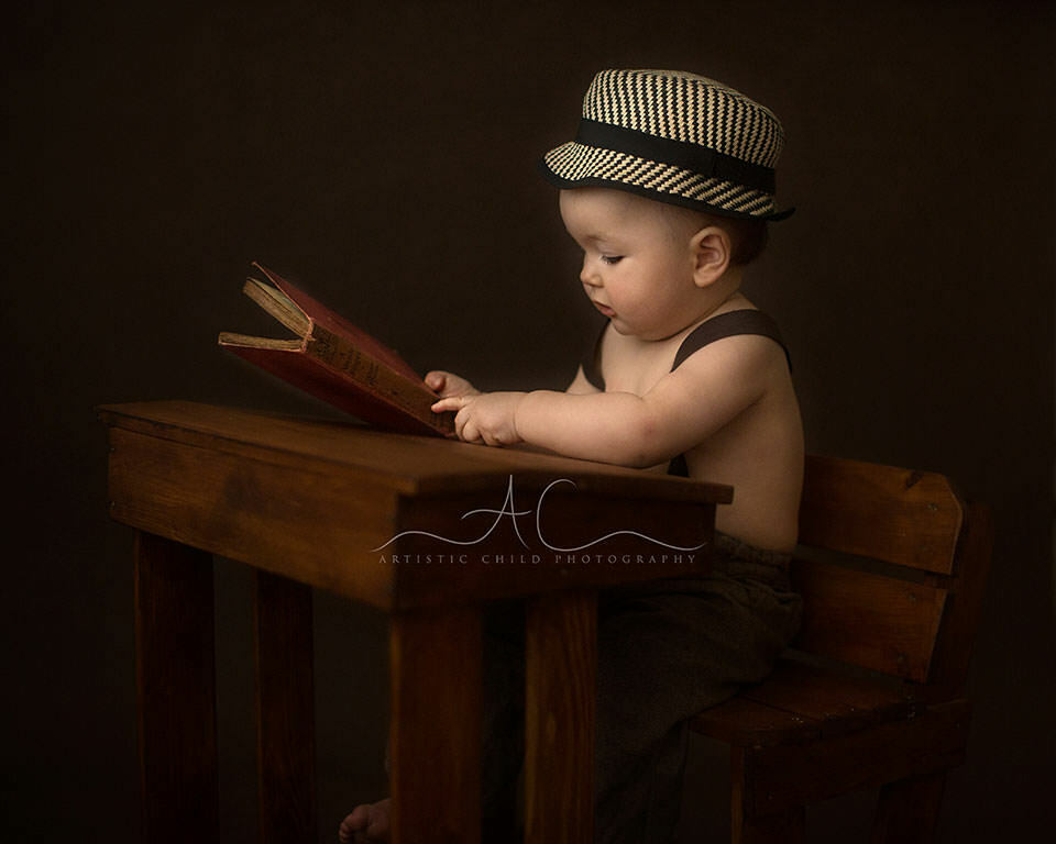 South East London Baby Photographer | baby boy looking intensly at the red book