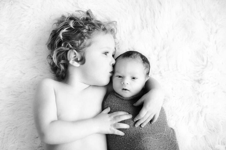 black and white portrait of 3 year old boy kissing his newborn baby brother | London
