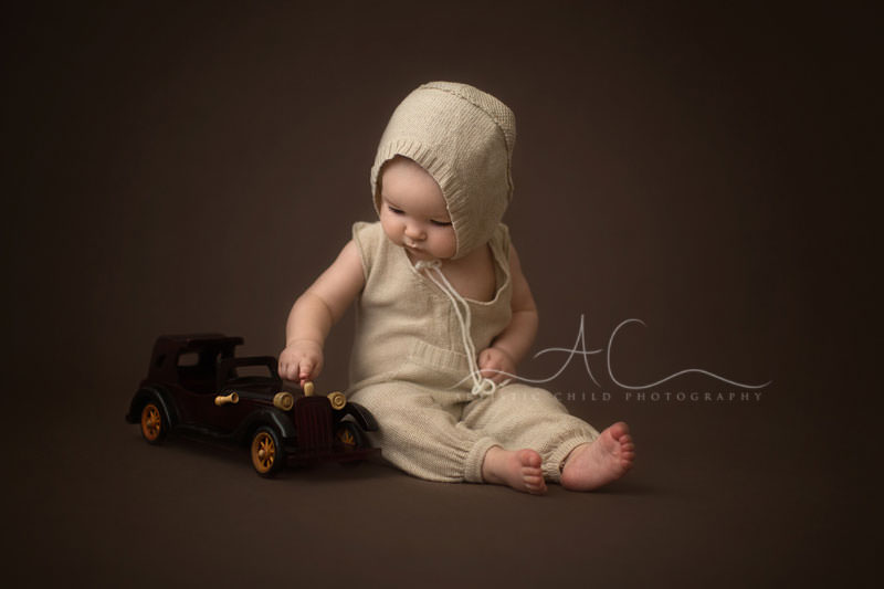 baby boy playing with old wooden car | London