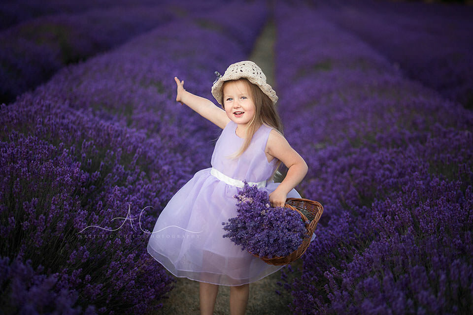 Best London Children Photos in Lavender Field | 4 year old girl holding a basket with lavender flowers and waving her hand