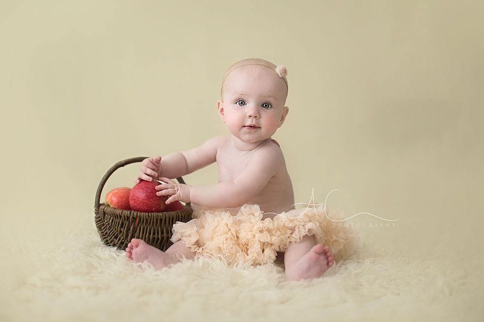 8 months old baby girl in tutu playing with apple wicker basket | London