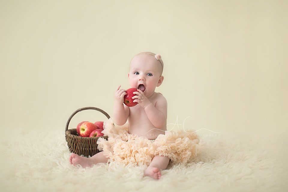photo of 8 months old baby girl  wearing tutu skirt and playing apples | London