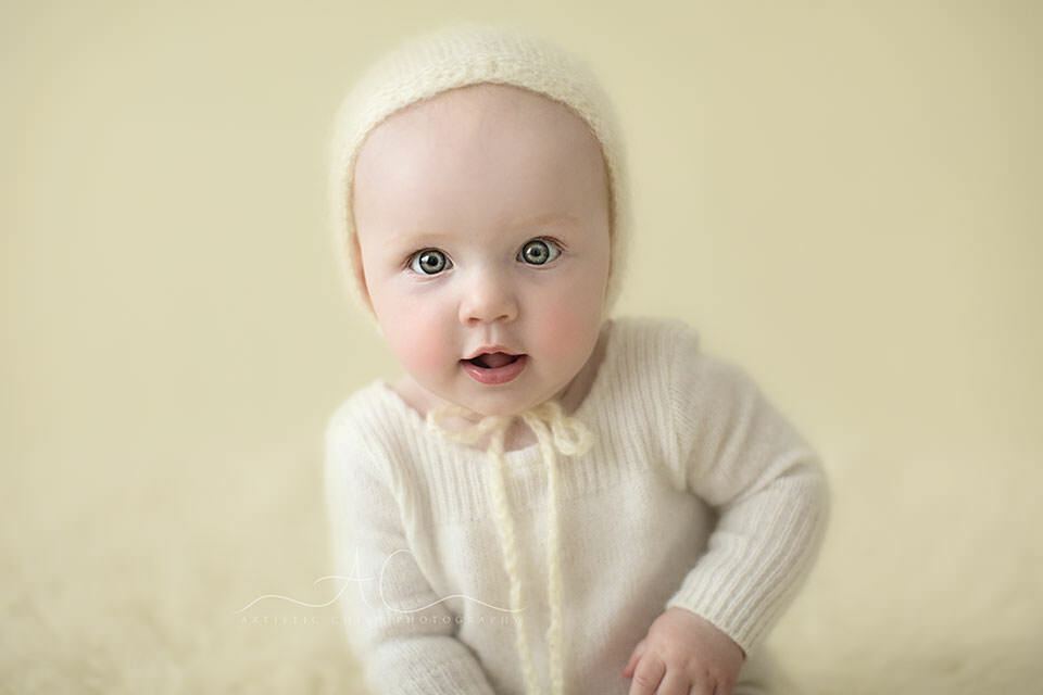 close up portrait of 8 months old baby girl wearing a cute white knitted hat | London