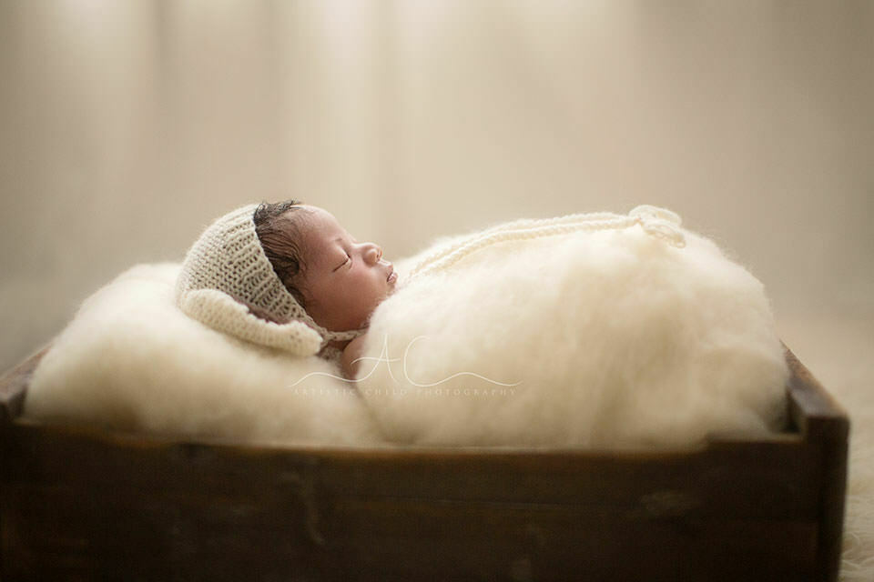 profile portrait of newborn baby boy sleeping in a crate   London