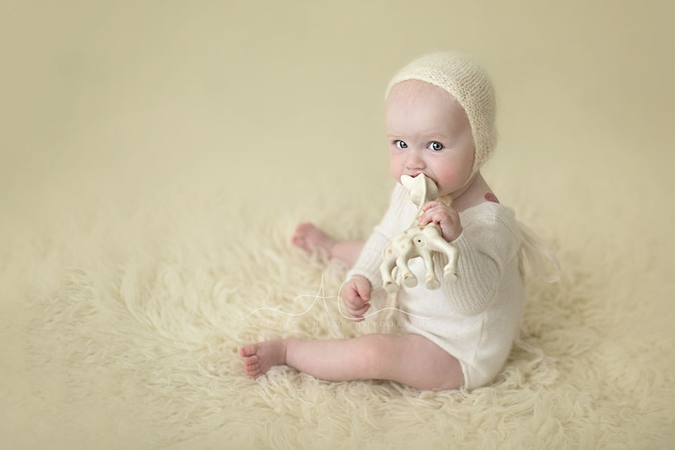 Professional London Baby Girl Photo Session | baby girl biting a Sophie prop