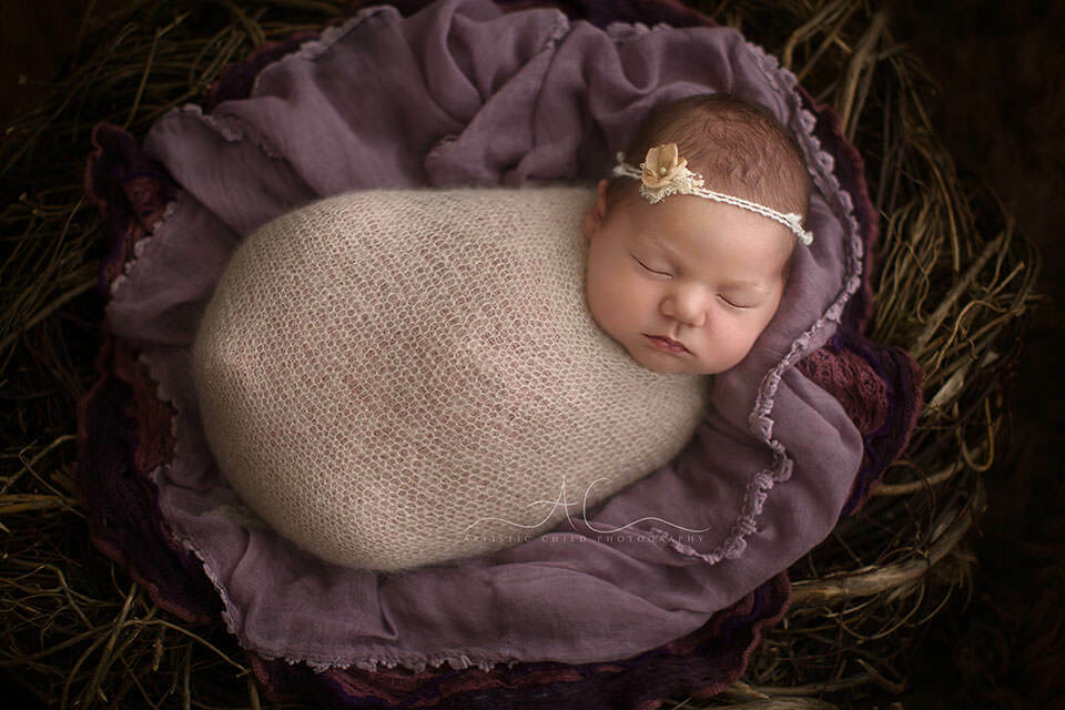 Portrait of wrapped newborn baby girl wearing a cute hairband london