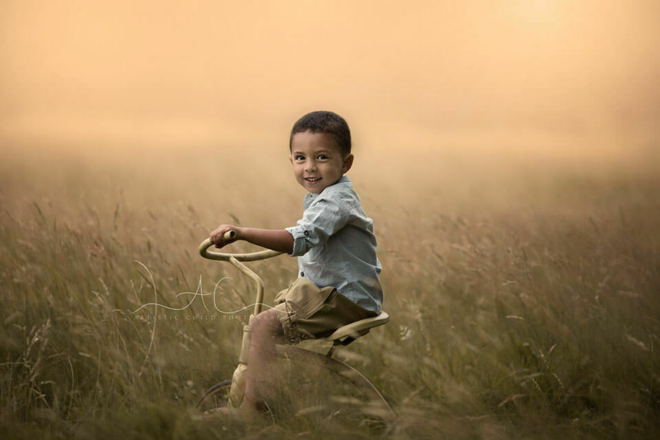London Child Photos | portrait of 3 year old boy on tricycle taken in Richmond Park