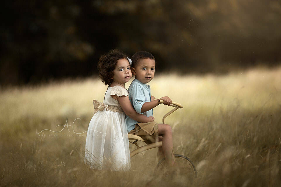 London Sibling Photographer | an outdoor portrait of a brother and sister on an old tricycle bike