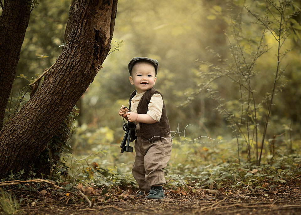 1 year old boy carrying a bunch of iron keys in the park during a photo session   London