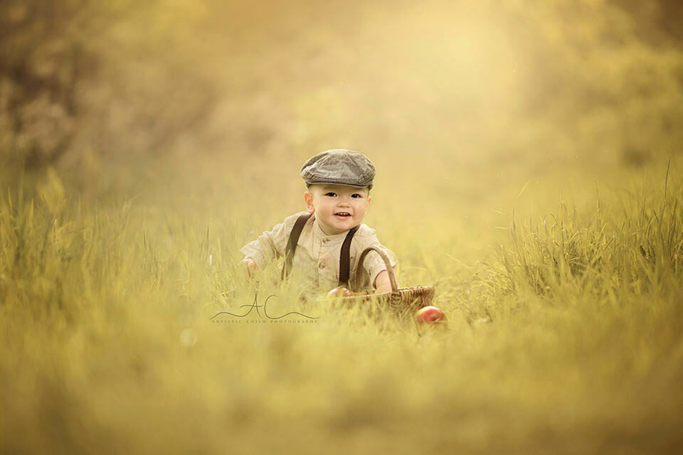 1 year old boy sitting in the grass and wearing a flat hat during a summer time | London