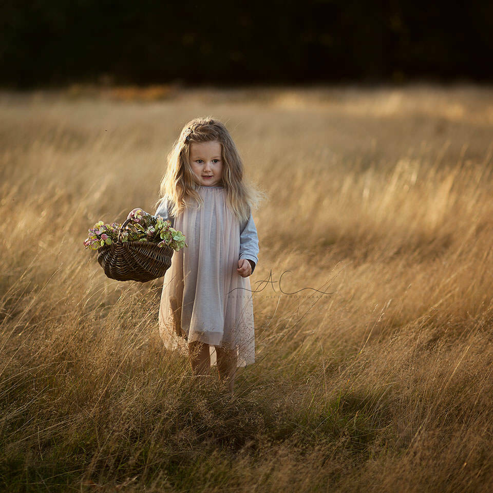 London Child Photography | photo of 3 year old girl holding a basket with flower in Richmond Park