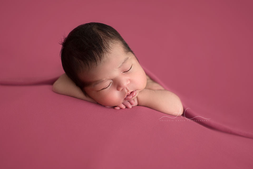 Natural Light London Newborn Images | newborn baby girl photographed on pink backdrop in chin on hands position