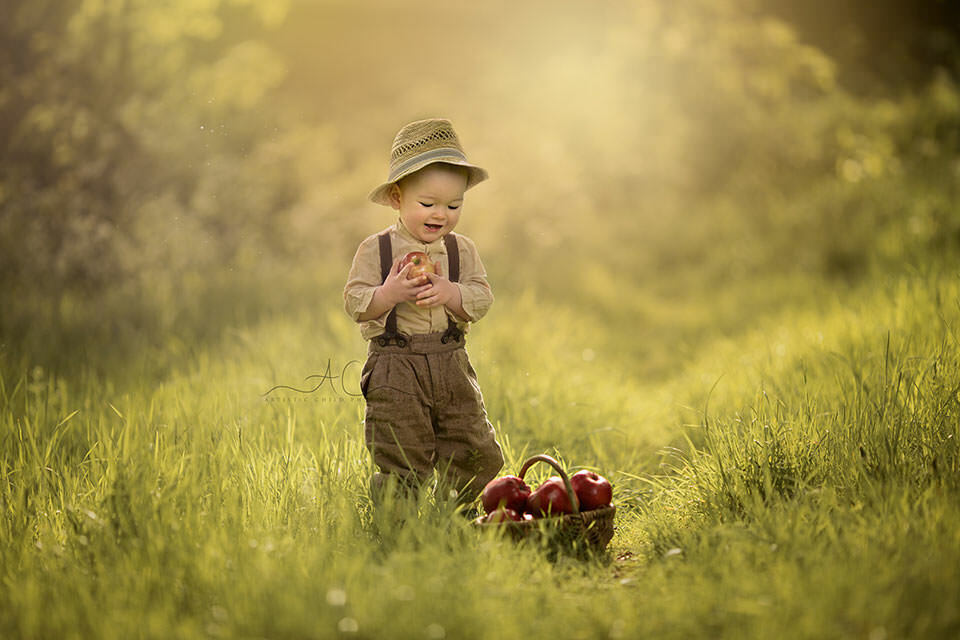 South East London Toddler Photos | portrait of 1 year old boy wearing a cute straw hat and playing with basket full of red apples