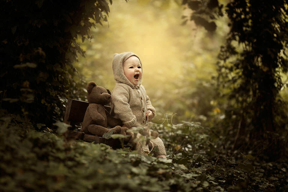Bromley Toddler Photographer | portrait of 1 year old boy yawning while sitting on little wooden bench next to his teddy bear