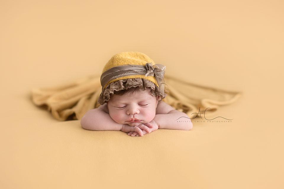 Natural Light London Newborn Photos | newborn baby girl wearing a cute little yellow hat