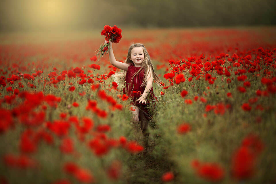 South East London Children Photos | 5 year old girl running through a poppy field and holding a bunch of poppy flowers