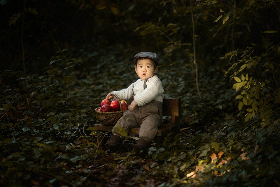 1 year old boy wearing a flat cap and playing with a basket of red apples in London park
