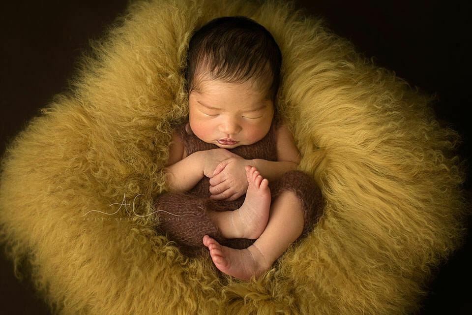 newborn baby boy sleeping on a curly sheepskin | London