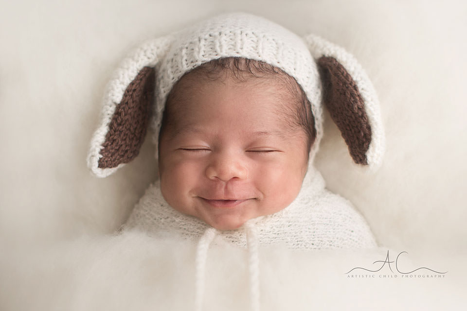 newborn baby boy wearing a funny ears hat and smiling   London